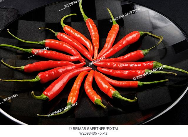 Close up of a ring of red hot Chili Peppers on a black plate