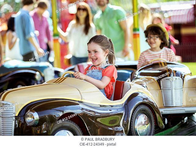 Cheerful girl on carousel in amusement park