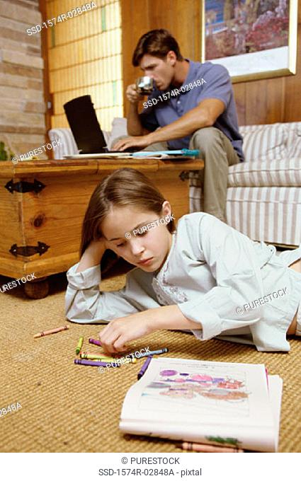 Girl lying on the floor with her father working on a laptop behind her