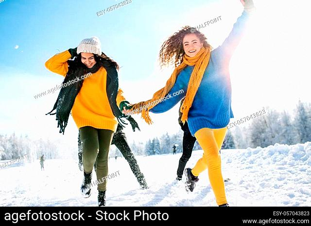 A group of young cheerful friends on a walk outdoors in snow in winter forest, holding hands and running