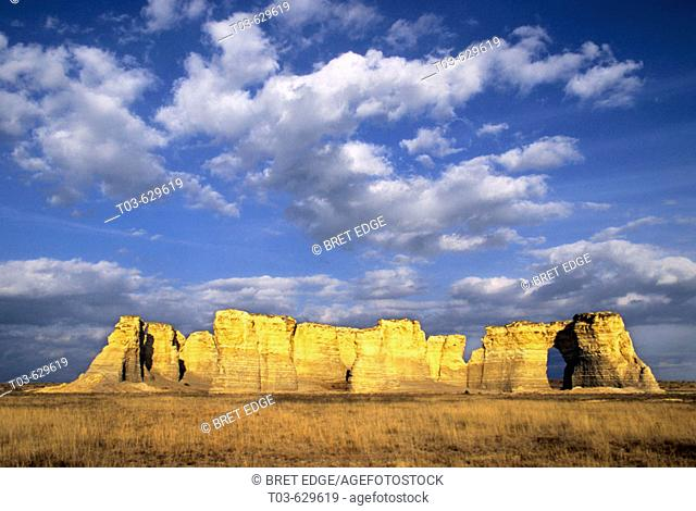 Once buried beneath an ancient sea, Monument Rocks rises from the plains below a sky filled with cottonball clouds, Kansas, USA