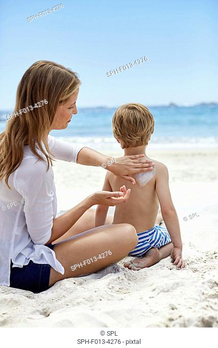 MODEL RELEASED. Mother applying sun cream to her son on the beach