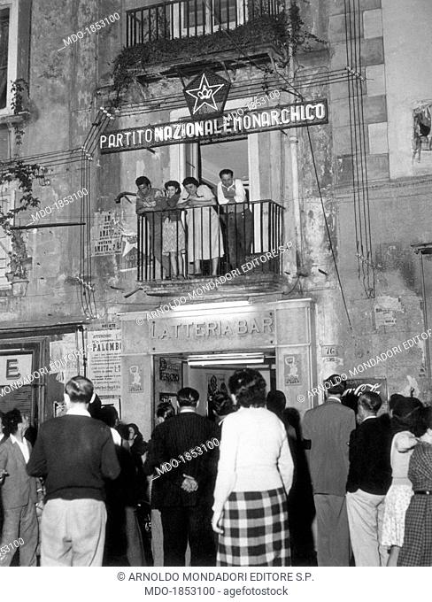 Some people looking out of the balcony of the Rione Forcella Monarchist National Party (PNM) local branch seat marked by a neon sign