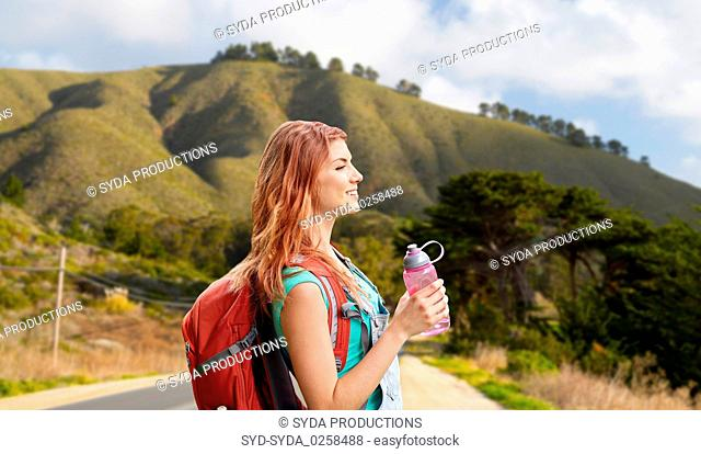 smiling woman with backpack on big sur hills