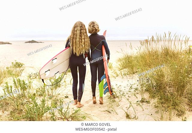 Spain, Aviles, rear view of two young surfers on the beach