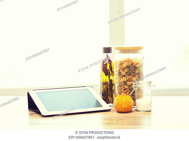 technology, internet and cooking concept - close up of tablet pc computer, olive oil, pasta, salt and pumpkin