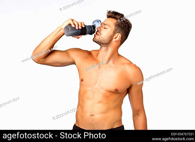 Sport, fitness and wellbeing concept. Handsome sexy young male athlete standing shirtless, holding water bottle and drinking with sassy arrogant expression