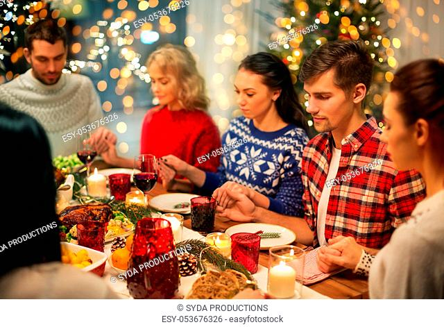 friends having home christmas dinner and praying