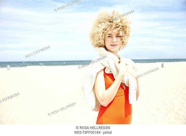 Portrait of young woman with curly blond hair on the beach