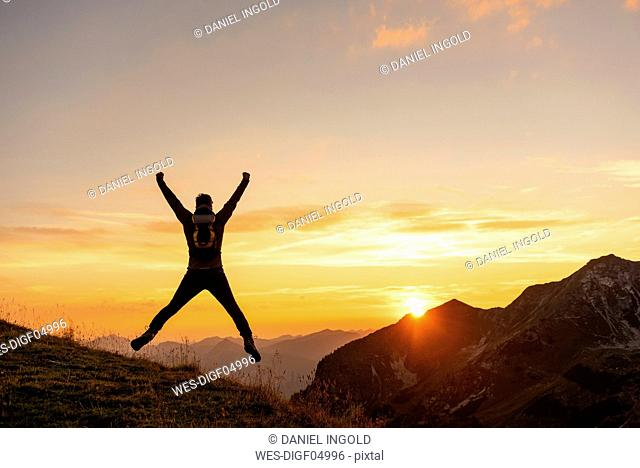 Germany, Bavaria, Oberstdorf, man on a hike in the mountains jumping at sunset