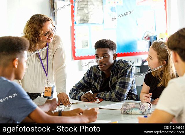 High school teacher talking with students at table in classroom