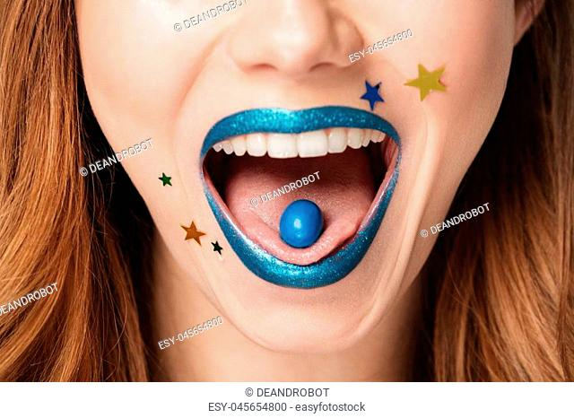 Close up portrait of a pretty brown haired woman with bright sparkling makeup with a blue candy in her mouth isolated over blue background