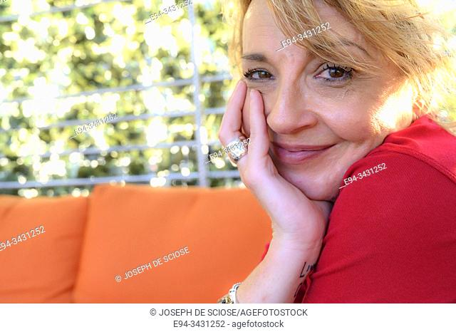 A 51 year old blond woman with hand on face, smiling at the camera