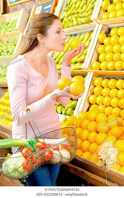 Young woman holding and smelling oranges from a stall