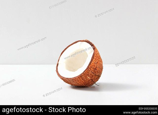 Natural organic tropical fruit half of ripe coconut on a light grey duotone background, copy space. Vegetarian concept