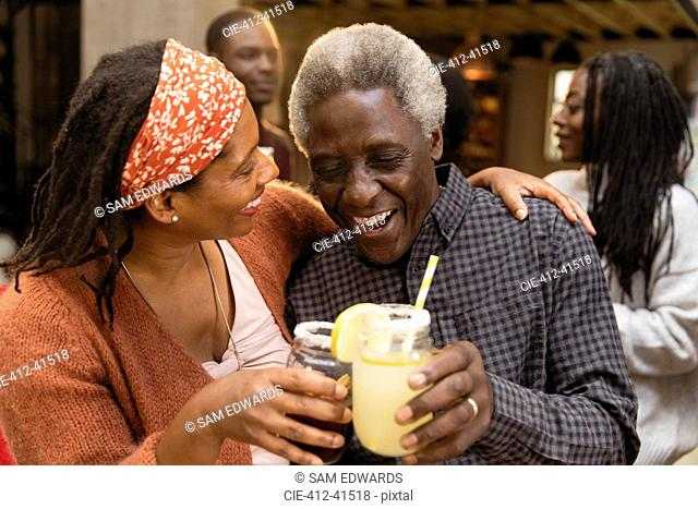 Senior father and daughter toasting lemonade, hugging on patio