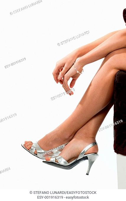 Close-up of a woman's legs and arms with elegant accessories