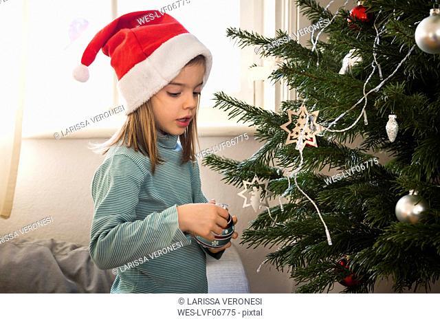 Little girl wearing Christmas cap decorating Christmas tree