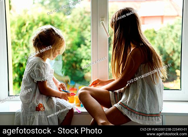 Two sisters playing plasticine by the window