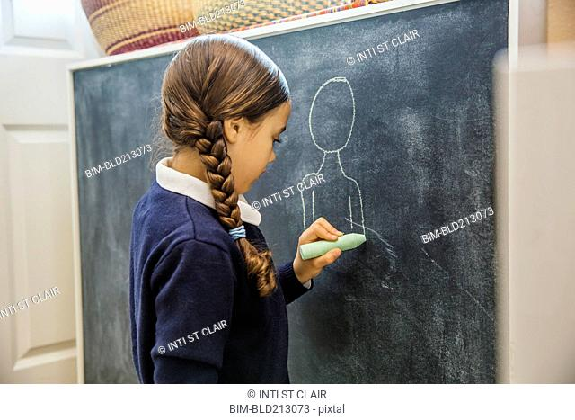 Mixed race girl drawing on chalkboard