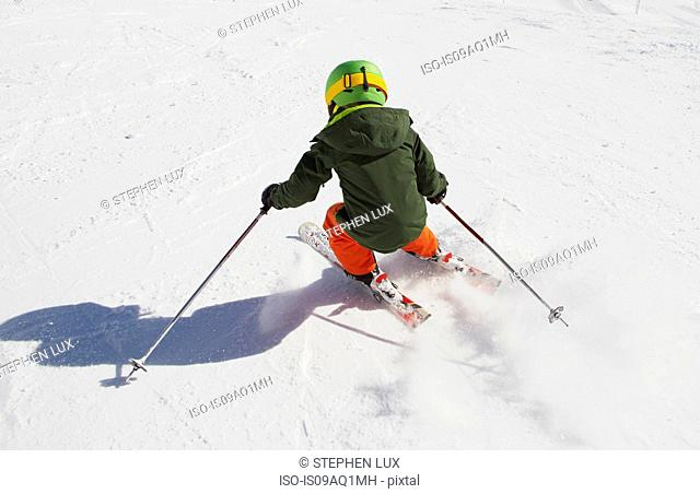 Young boy skiing downhill, rear view