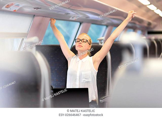 Businesswoman traveling by train, streching her upper body arms reised taking a break from laptop work. Business travel concept