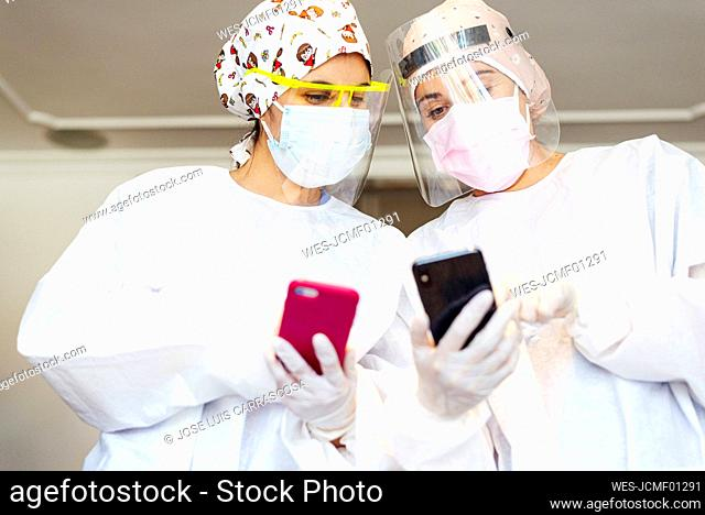 Dentist and assistant using mobile phone while standing at office