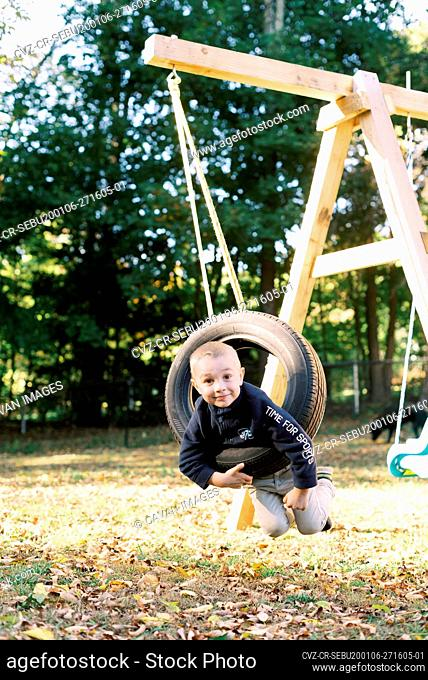 Little boy playing with a tire swing