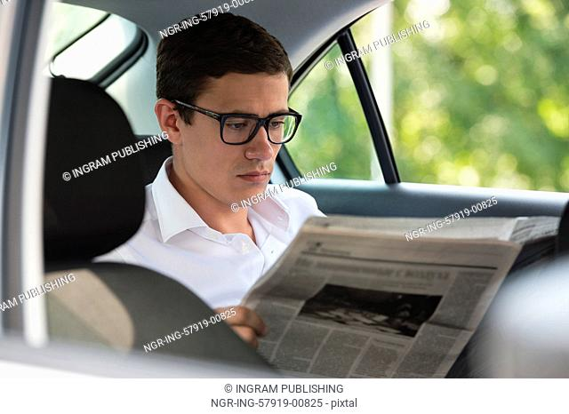 Businessman reading news in his car