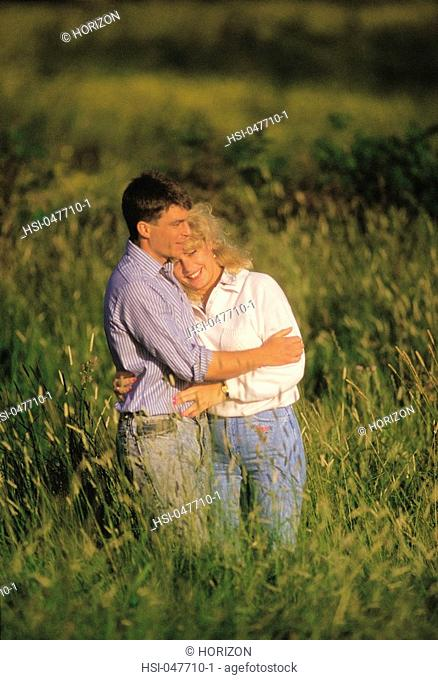 Young smiling couple hugging and standing in a field