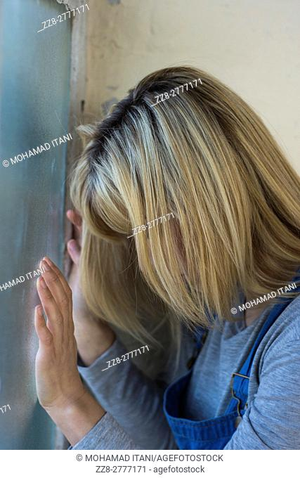 Profile of a depressed young woman leaning on the window