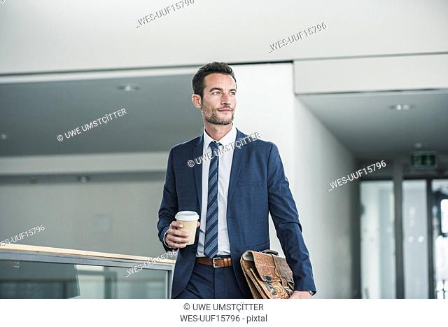 Businessman with briefcase walking in office building, holding cup of coffee