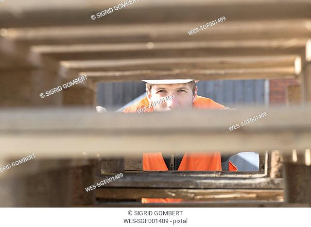 Construction worker looking through stack of pallets