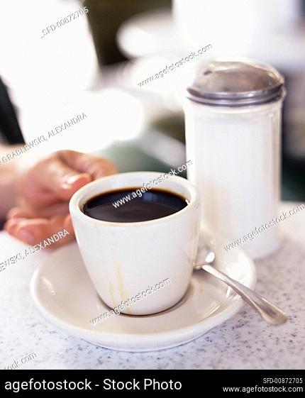 Cup of coffee, sugar shaker