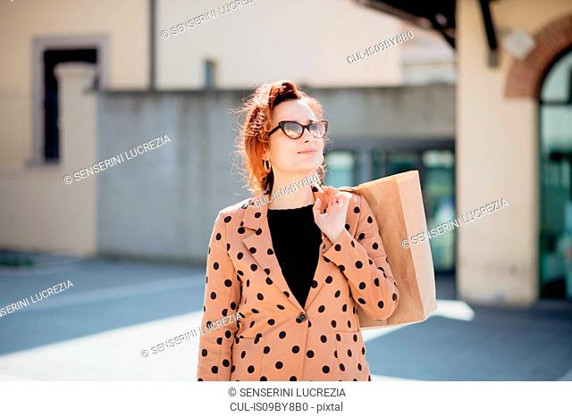 Female shopper sightseeing in piazza, Arezzo, Toscana, Italy