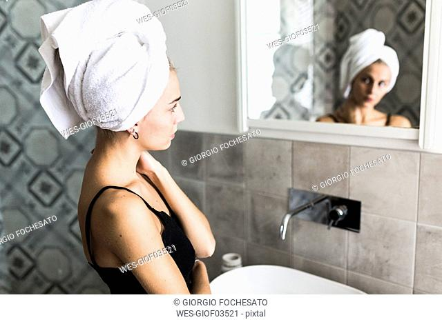 Young woman with hair wrapped in a towel looking in bathroom mirror