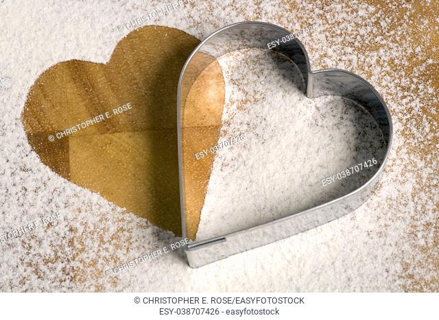 Heart shaped cookie cutter on a a flour dusted worktop