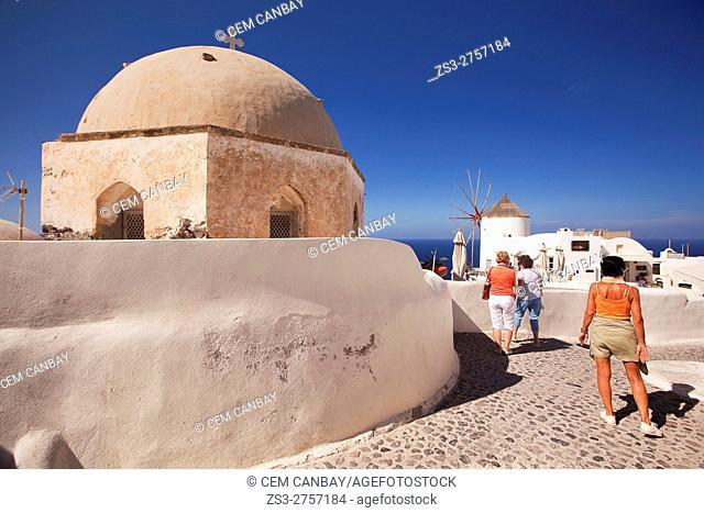 Tourists near the church and the traditonal windmill in Oia village, Santorini, Cyclades Islands, Greek Islands, Greece, Europe