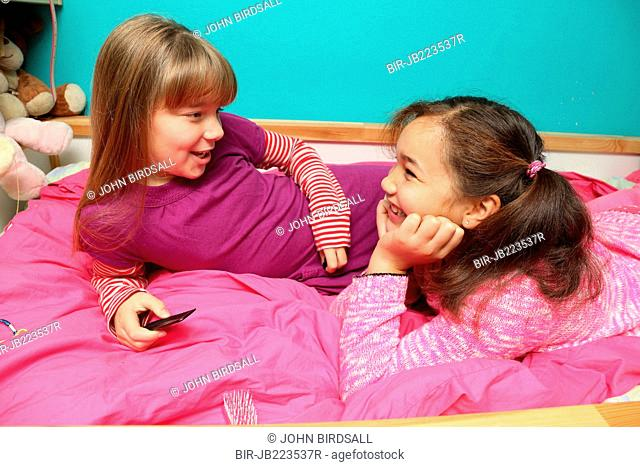 Young girls chatting in bedroom