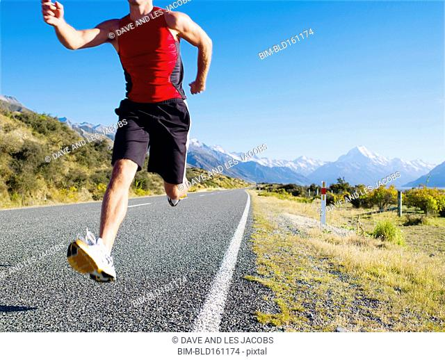 Mixed race man running on remote road