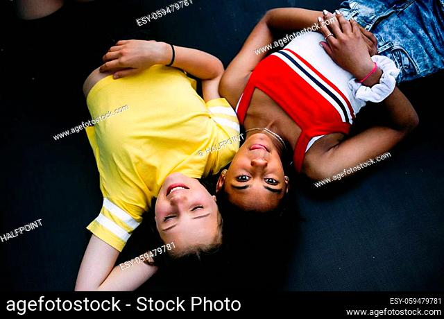 Top view of cheerful young teenager girls friends outdoors in garden, looking at camera