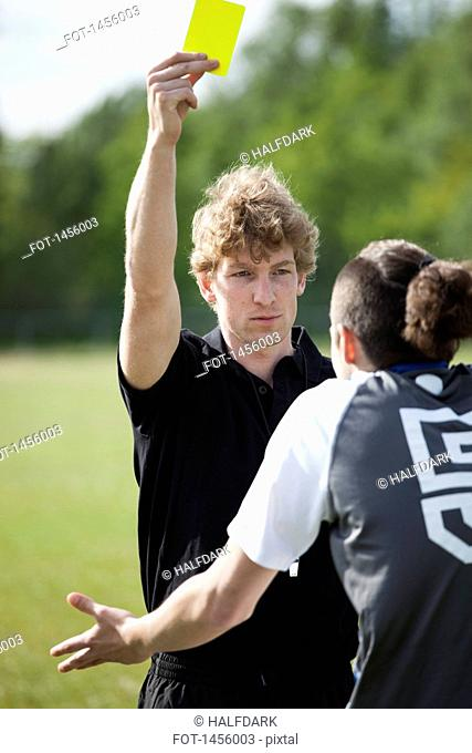 Referee showing yellow card to soccer player