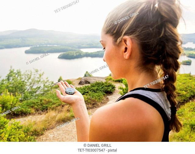 Young woman holding compass
