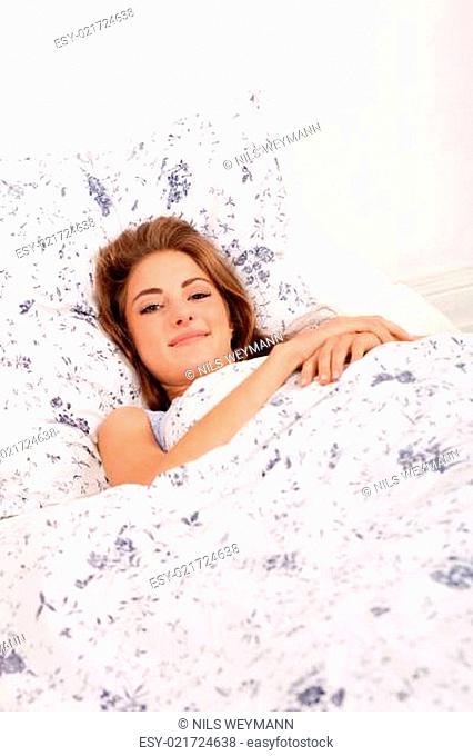 junge attraktive frau liegt im bett morgens schlafend