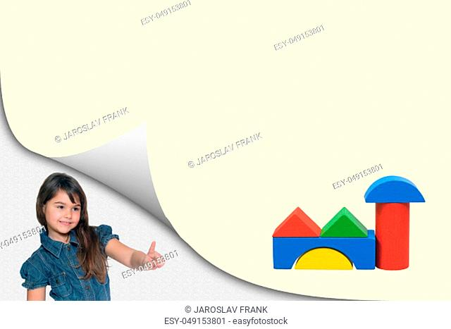 Building concept. Cute tanned little girl is showing at a blank yellow page with curl effect with a building toy created from colorful wooden cubes ready for...