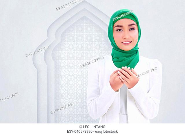 Smiling asian muslim woman raising hand and pray with white wall background