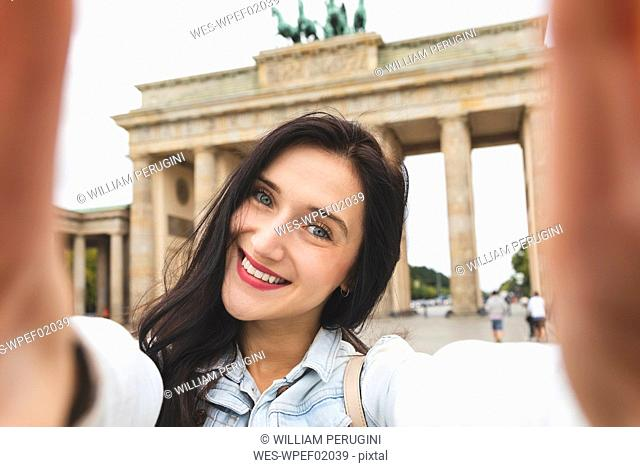 Selfie of happy young woman at Brandenburg Gate, Berlin, Germany