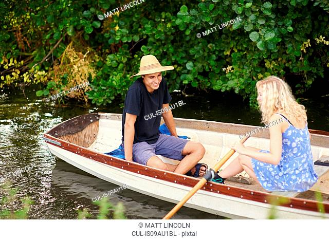 Young couple rowing river rowing boat