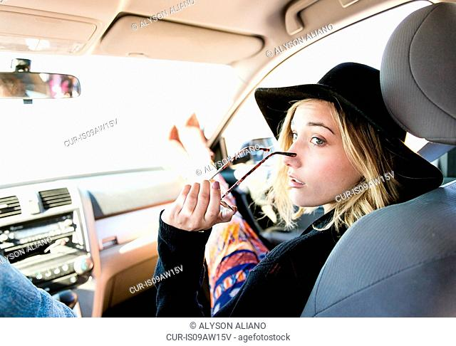 Over the shoulder view of young woman in car wearing hat looking away, holding sunglasses