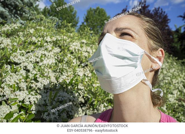 Young woman with protective mask at blooming park with half-closed eyes because of the strong sun